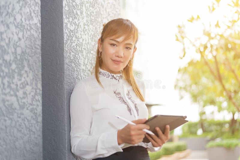 Aziatische Bedrijfsvrouw, Vrouwentribune en glimlach die glimlachen, die op witte achtergrond, Vrouw het werk concept wordt geïso stock fotografie