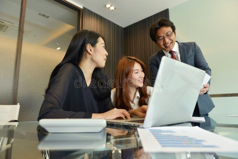 Aziatische Bedrijfsvrouwen die aan hun werkgever in bureau spreken royalty-vrije stock afbeeldingen