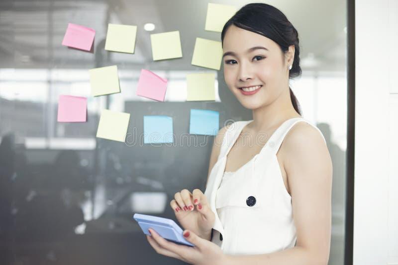 Aziatische bedrijfsvrouwen die en aan muurglas glimlachen samenwerken royalty-vrije stock afbeelding