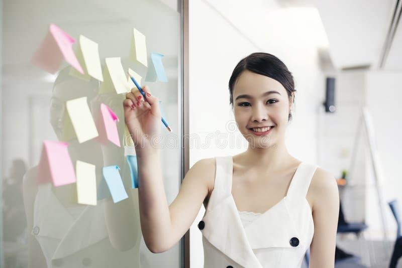 Aziatische bedrijfsvrouwen die en aan muurglas glimlachen samenwerken royalty-vrije stock foto's