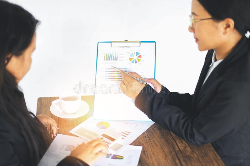 Aziatische bedrijfsvrouwen die heden werken de financiële informatie van de rapportgrafiek op de vergadering in bureau het lijstb stock afbeeldingen