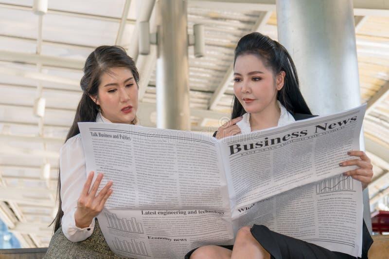 Aziatische bedrijfsvrouwen die krant samen lezen stock foto
