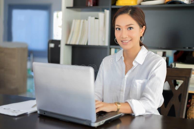 Aziatische bedrijfsvrouwen notitieboekje gebruiken en glimlachen die gelukkig voor worki royalty-vrije stock afbeeldingen