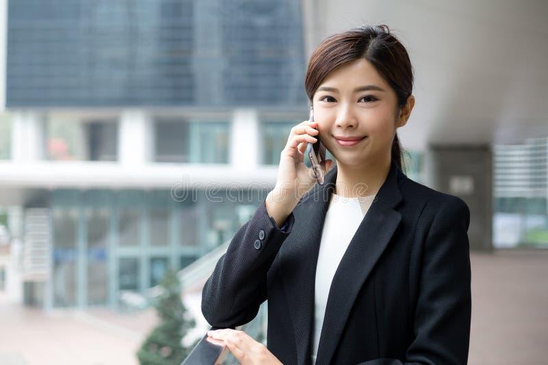 Aziatische bedrijfsvrouwenbespreking aan mobiele telefoon royalty-vrije stock fotografie