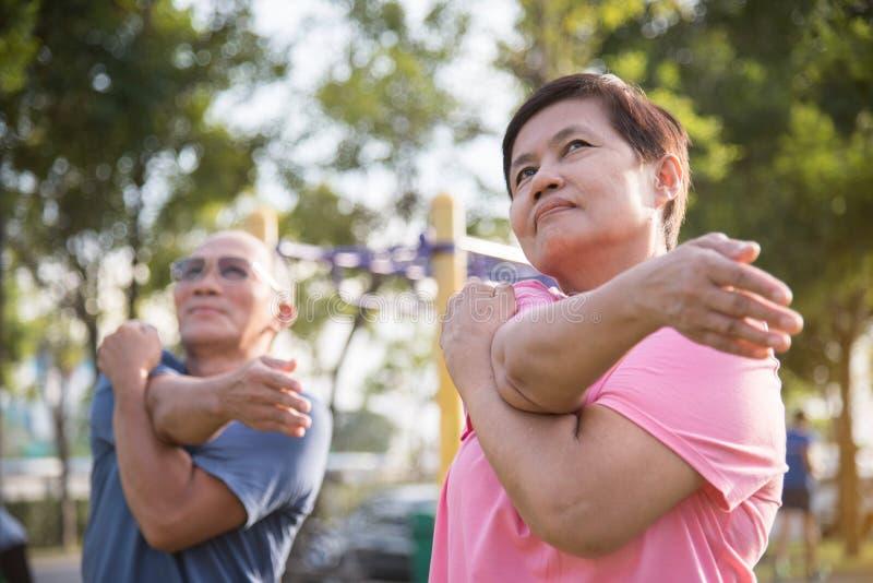Aziatische bejaarde mensen die zich vóór oefening uitrekken royalty-vrije stock foto