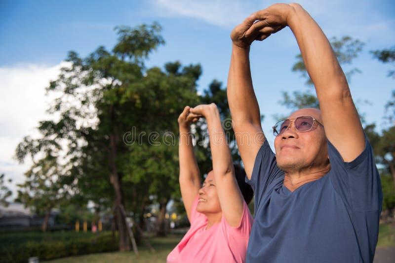 Aziatische bejaarde mensen die zich vóór oefening uitrekken royalty-vrije stock afbeeldingen