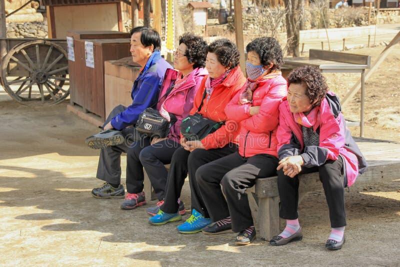 Aziatische bejaarde toeristen bij groep het sightseeing in Koreaans volksdorp stock foto's