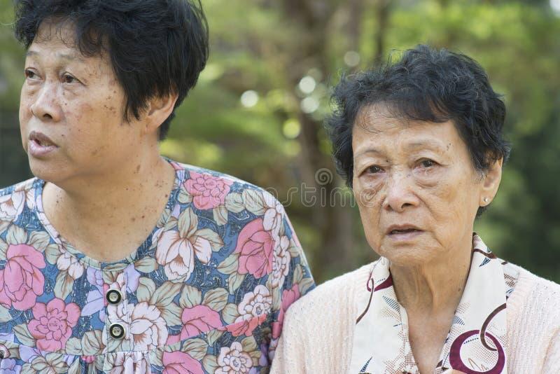 Aziatische bejaarden die bij openlucht spreken stock fotografie
