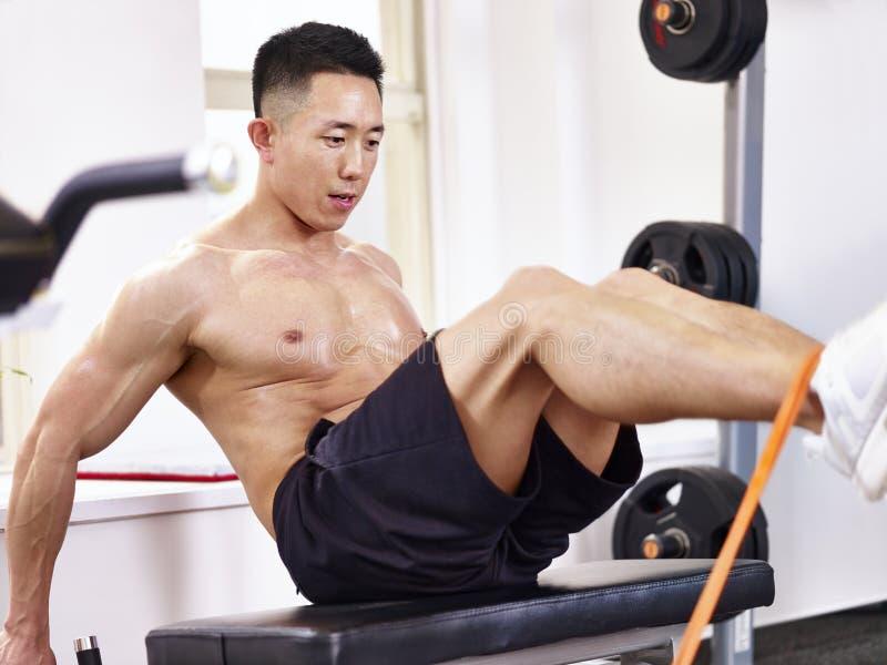 Aziatische bodybuilder die in gymnastiek uitoefenen stock foto's