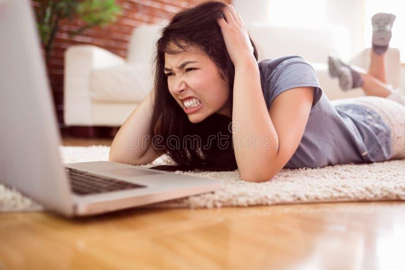 Aziatische boze vrouw die laptop op vloer met behulp van stock foto's