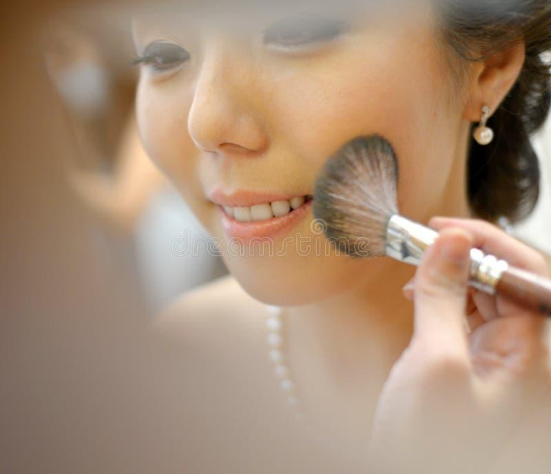 Aziatische bruid die huwelijkssamenstelling toepassen stock afbeeldingen