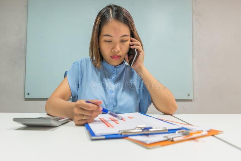 Aziatische bureaumanager die op telefoon over de financiën spreken royalty-vrije stock fotografie
