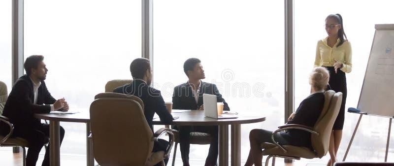 Aziatische buspresentator die aan divers team op groepsvergadering spreken royalty-vrije stock afbeelding