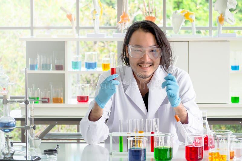 Aziatische chemicusmens die vloeibare substantie in reageerbuizen controleren stock afbeeldingen
