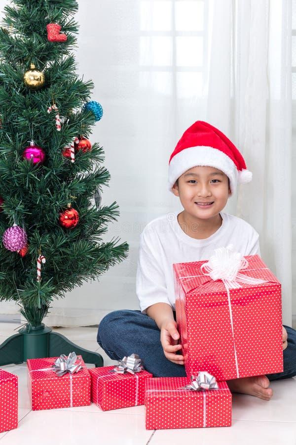 Aziatische Chinees weinig doos van de Kerstmisgift van de jongensholding royalty-vrije stock afbeelding