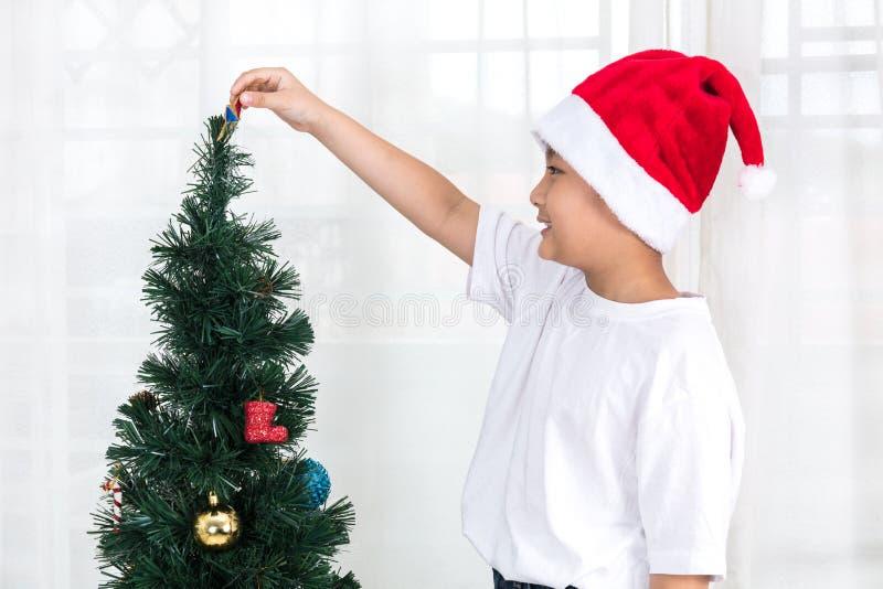 Aziatische Chinees weinig jongen die Kerstboom thuis verfraaien royalty-vrije stock afbeelding
