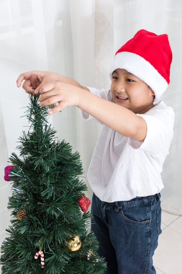 Aziatische Chinees weinig jongen die Kerstboom thuis verfraaien stock afbeeldingen