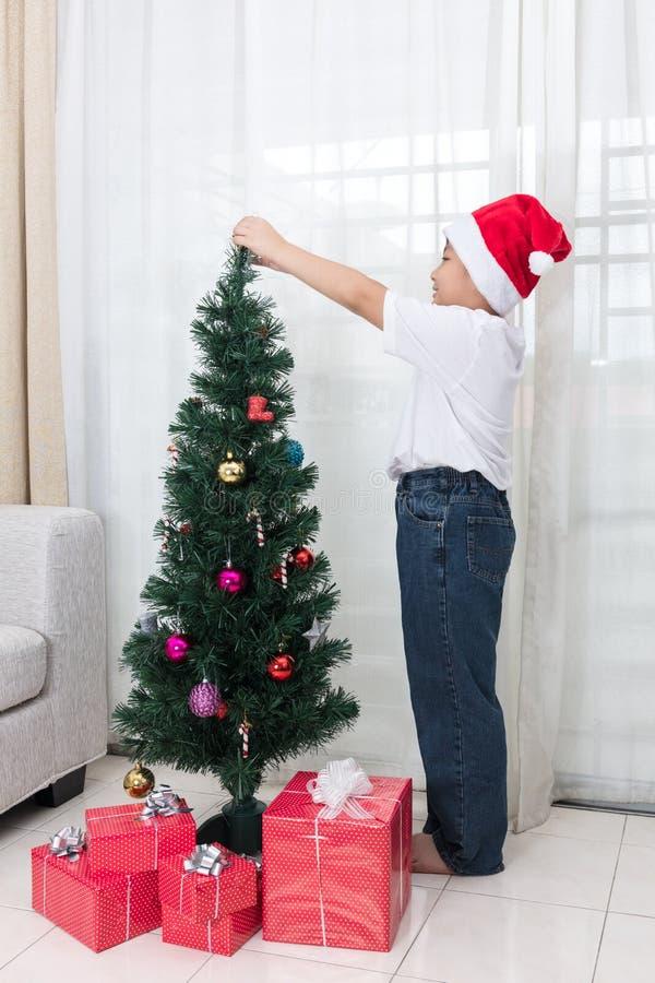 Aziatische Chinees weinig jongen die Kerstboom thuis verfraaien royalty-vrije stock afbeeldingen