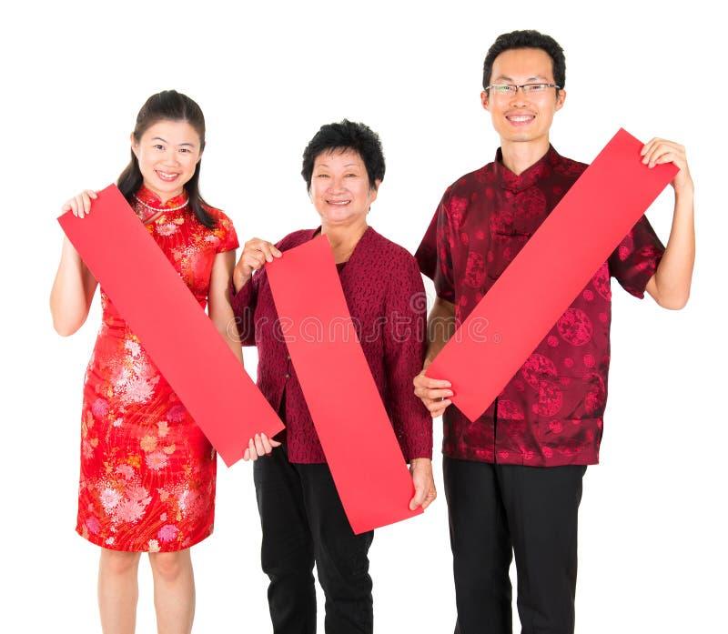 Aziatische Chinese familie die de rode lentecoupletten houden royalty-vrije stock foto