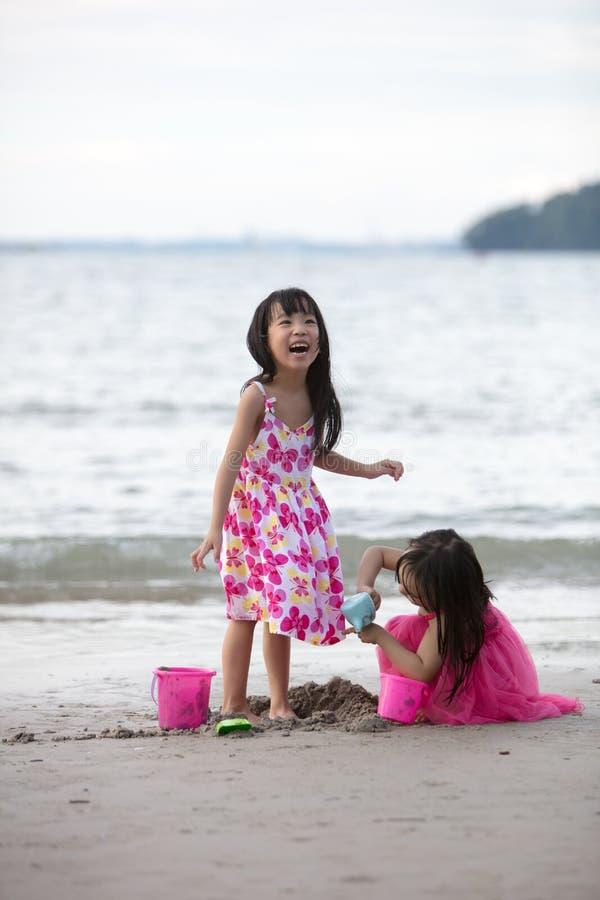 Aziatische Chinese kleine zusters die zand spelen stock foto