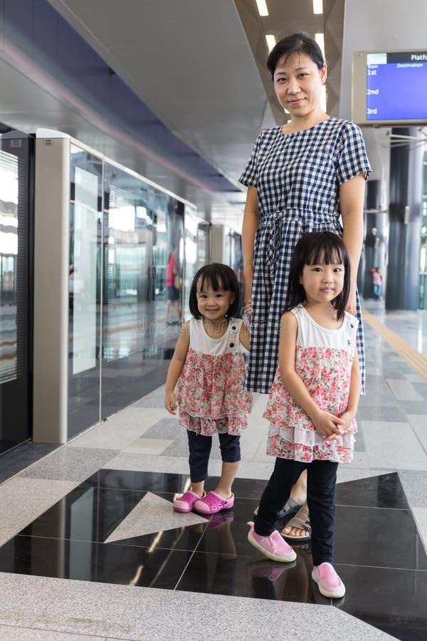 Aziatische Chinese moeder en dochters die op doorgang bij statio wachten stock foto's