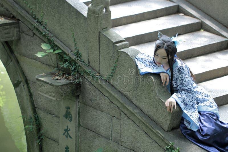 Aziatische Chinese vrouw in traditionele Blauwe en witte Hanfu-kleding, spel in een beroemde tuin royalty-vrije stock foto