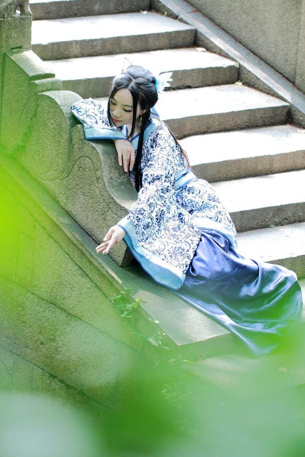 Aziatische Chinese vrouw in traditionele Blauwe en witte Hanfu-kleding, spel in een beroemde tuin stock afbeelding