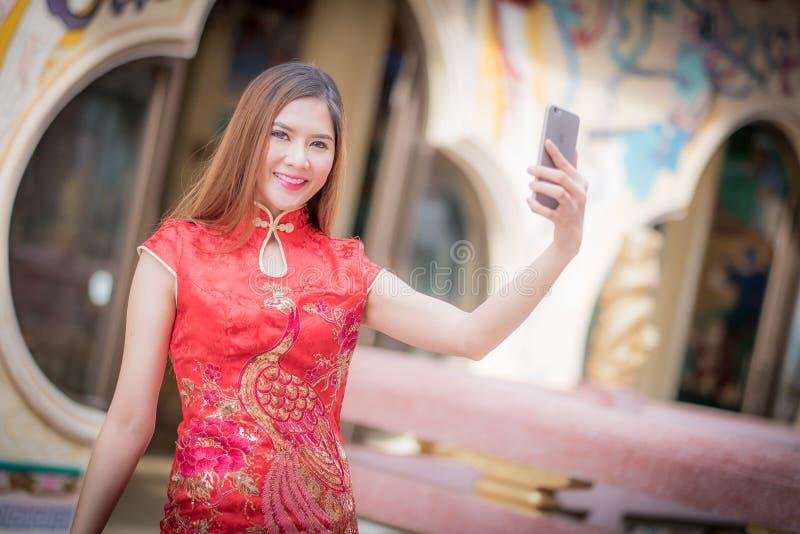 Aziatische Chinese vrouw in Traditionele Chinese en greeptelefoon royalty-vrije stock foto
