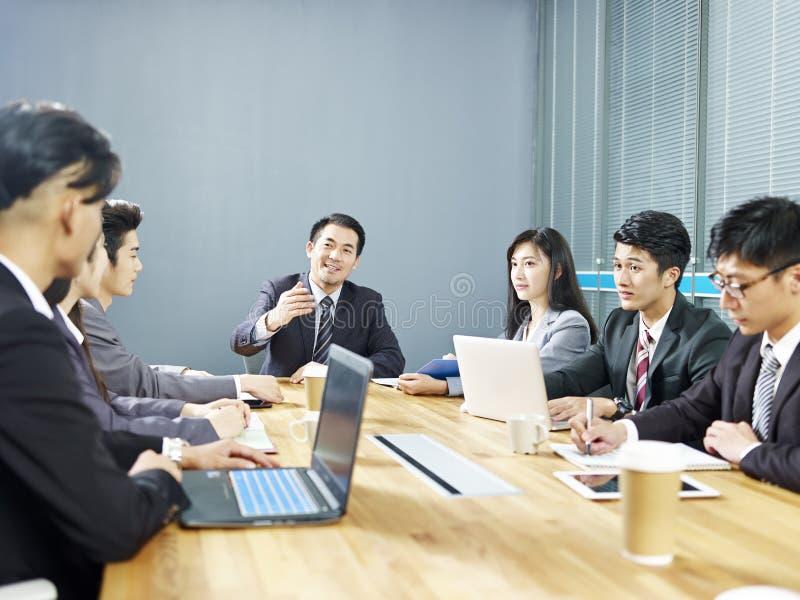Aziatische collectieve bedrijfsmensen die in bureau samenkomen stock foto
