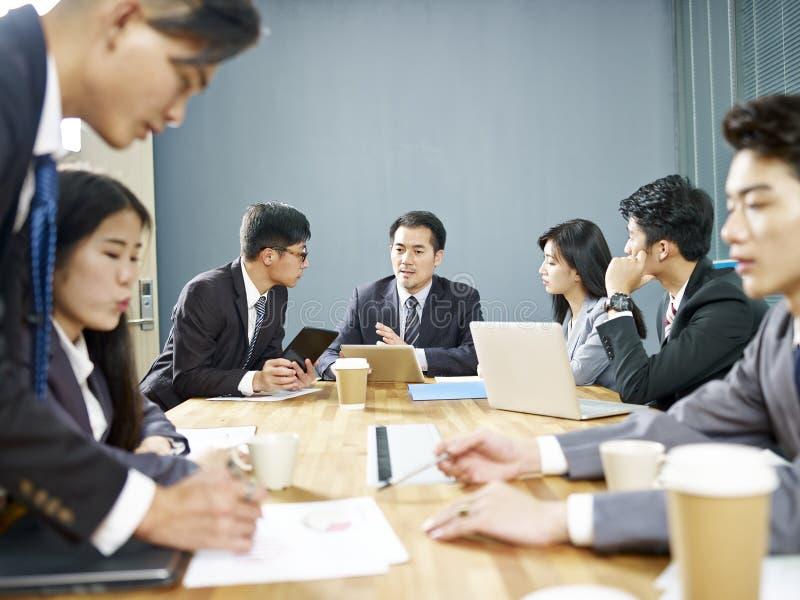 Aziatische collectieve mensen die zaken in vergadering bespreken stock afbeelding