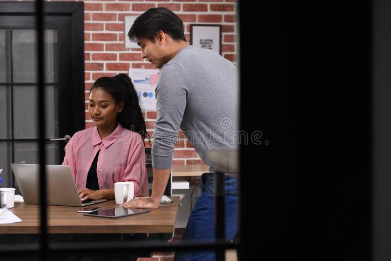 Aziatische collega's die het werk bespreken die laptop in het bureau met behulp van stock afbeelding