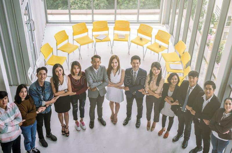 Aziatische commerciële teamcollega's met Holdingshanden die zich in bureau bevinden de greephanden van het bedrijfsmensenteam sam stock foto's