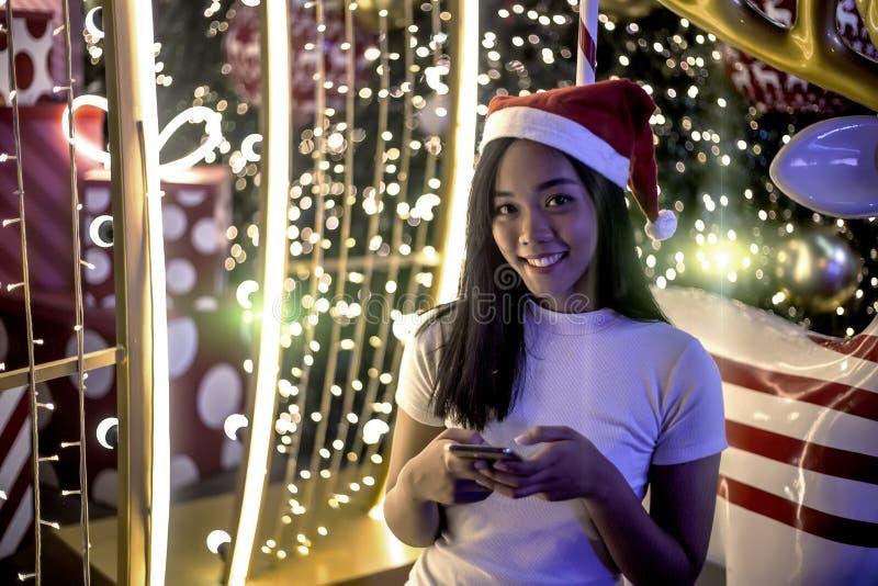 Aziatische dameglimlach met nacht lichte decoratie in santahoed en mobiel aan mededeling stock afbeeldingen