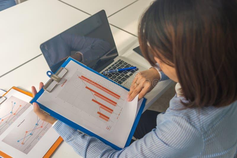 Aziatische de verkooprapporten van de bedrijfsleiderlezing in de bedrijfsruimte royalty-vrije stock foto
