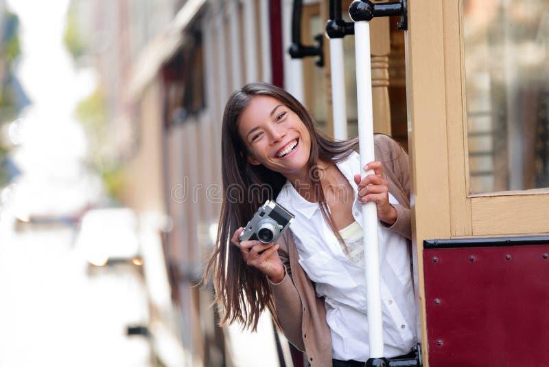 Aziatische de vrouwentoerist die van de reislevensstijl het beroemde systeem van de tramspoorkabelwagen in de stad van San Franci stock afbeelding