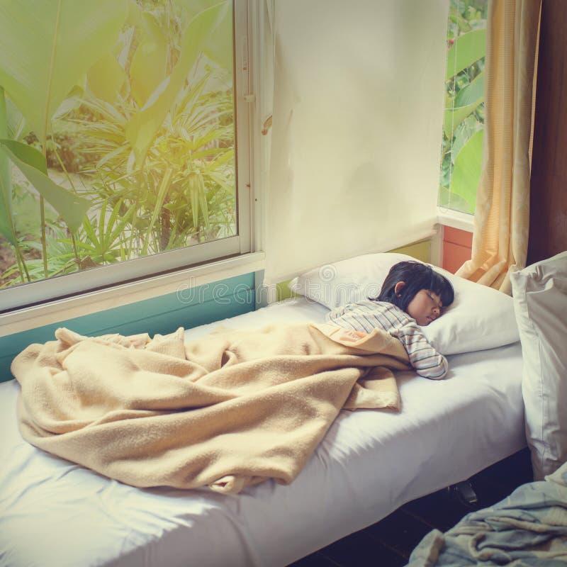 Aziatische die meisjesslaap op bed met deken wordt behandeld royalty-vrije stock afbeeldingen