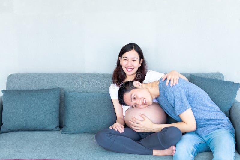 Aziatische die mens tegen aan babybuil wordt geleund van zijn zwangere vrouw royalty-vrije stock afbeeldingen