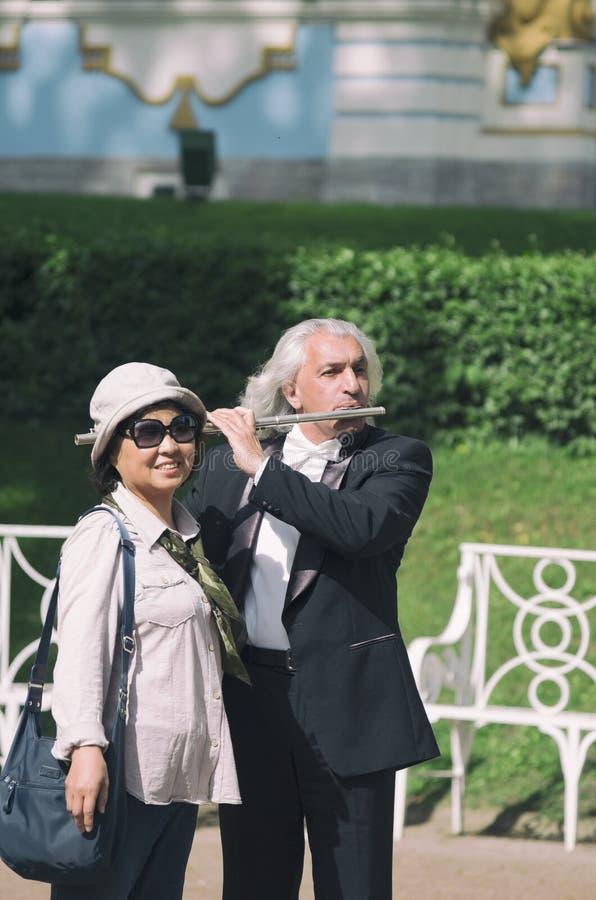 Aziatische die vrouw met een straatmusicus wordt gefotografeerd royalty-vrije stock foto