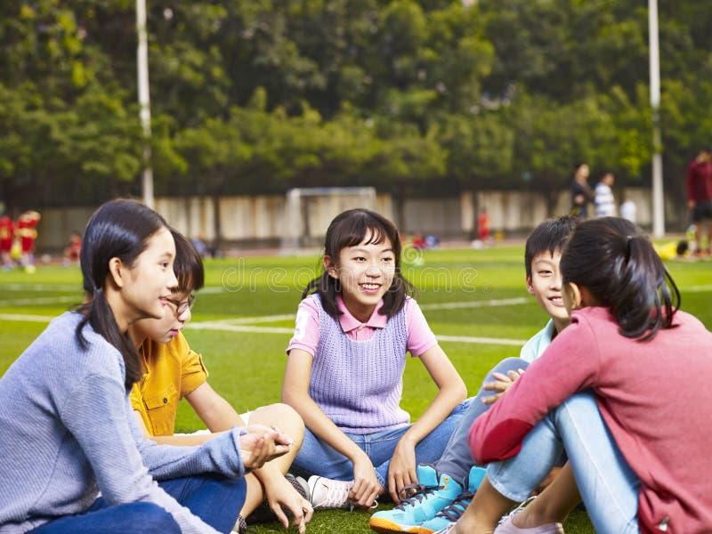 Aziatische elementaire schoolkinderen die en op gras aanwezig zijn babbelen stock afbeeldingen