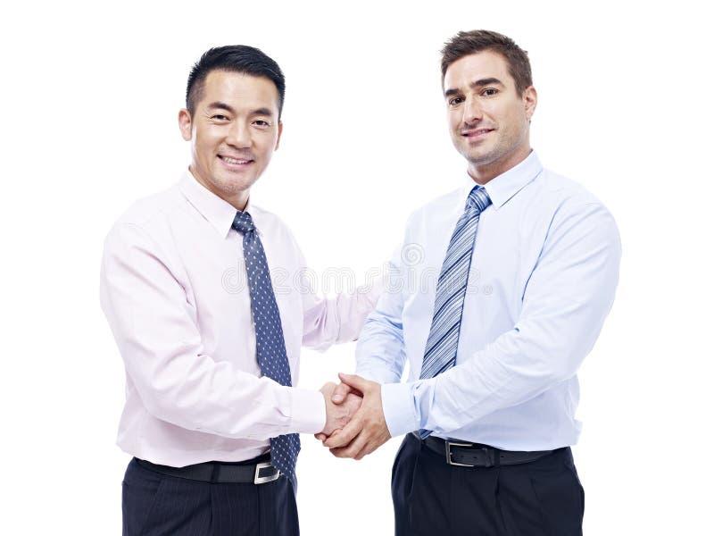 Aziatische en Kaukasische zakenlieden die handen schudden stock afbeeldingen