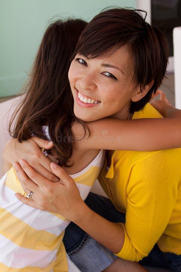 Aziatische en Moeder en dochter die glimlachen koesteren stock fotografie