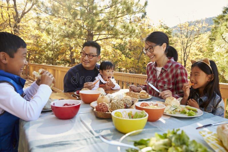 Aziatische familie die buiten bij een lijst aangaande een dek in een bos eten royalty-vrije stock afbeelding