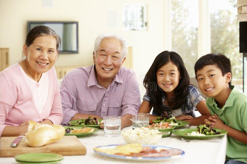 Aziatische familie die maaltijd thuis delen stock fotografie