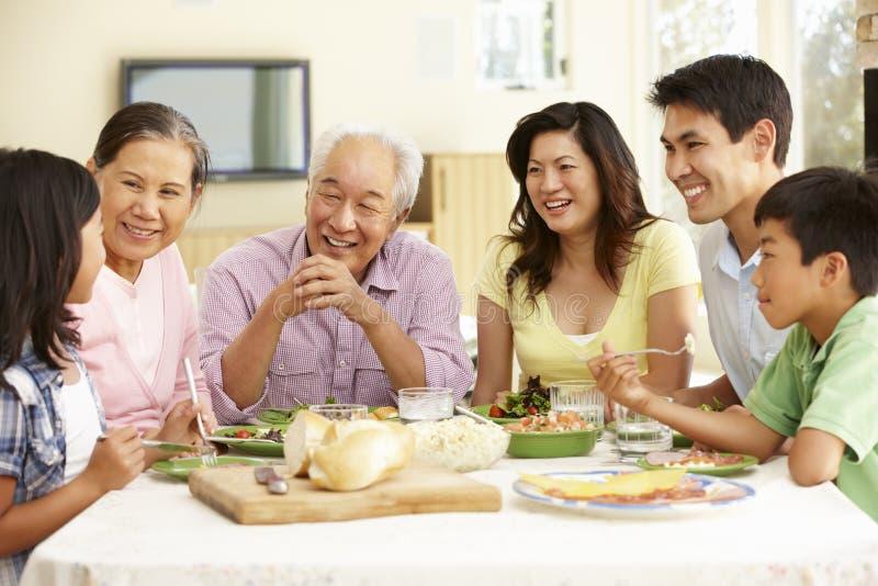 Aziatische familie die maaltijd thuis delen stock afbeelding