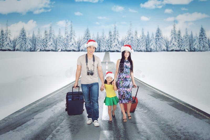 Aziatische familie die op de sneeuwweg lopen royalty-vrije stock fotografie