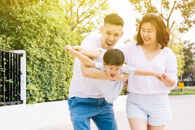 Aziatische familie die pret hebben en een kind in openbaar park vervoeren royalty-vrije stock afbeelding