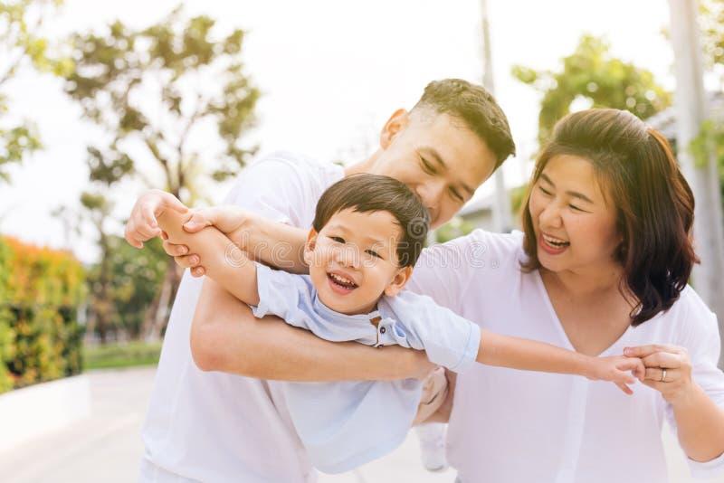 Aziatische familie die pret hebben en een kind in openbaar park vervoeren stock foto's