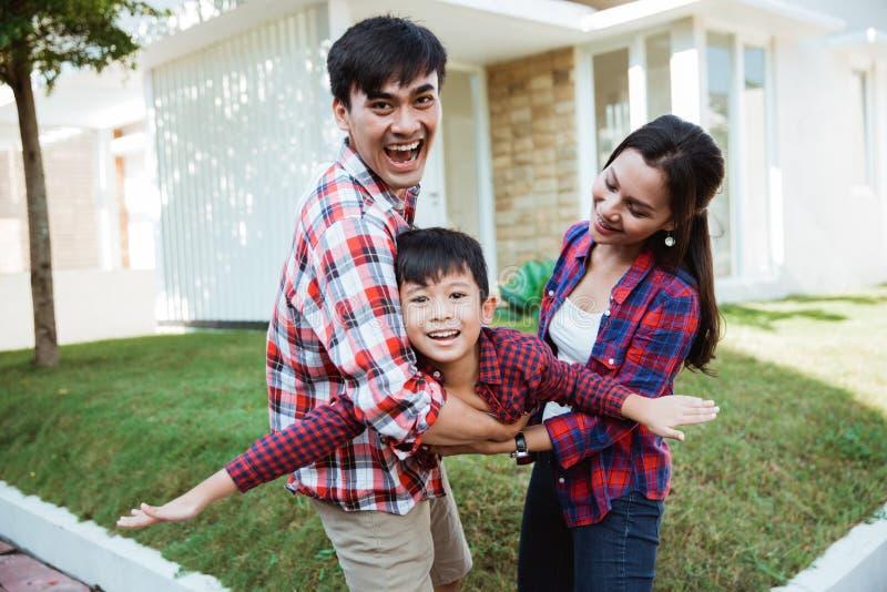 Aziatische familie met jong geitjeportret voor hun huis stock foto's