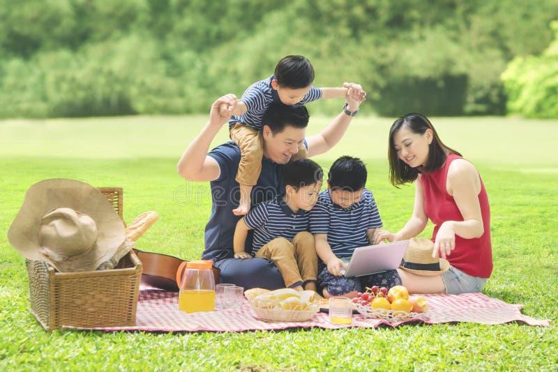 Aziatische familie met laptop in het park royalty-vrije stock foto