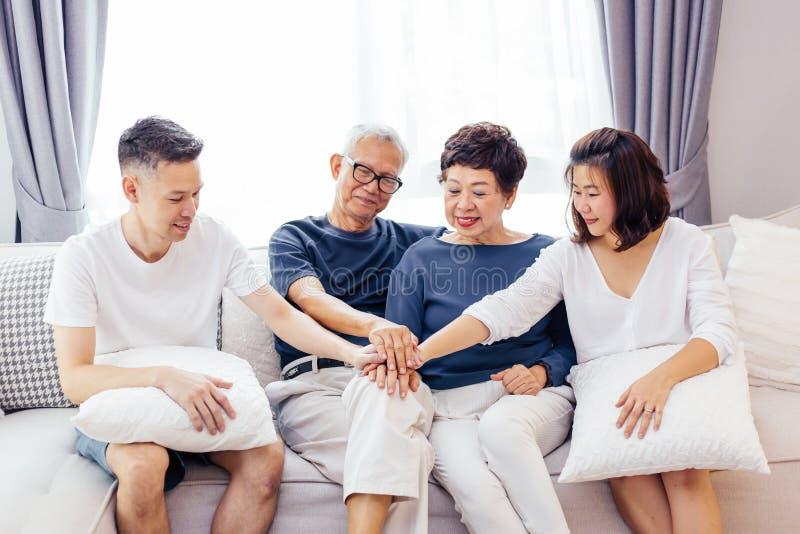 Aziatische familie met volwassen kinderen en hogere ouders die handen samenbrengen en op bank thuis samen zitten Familieeenheid royalty-vrije stock afbeelding